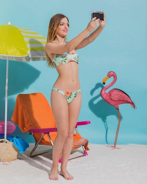 Hermosa mujer en bikini haciendo selfie Foto gratis