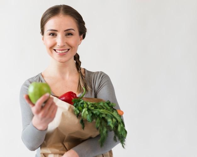 Hermosa mujer con bolsa de papel con frutas y verduras Foto gratis