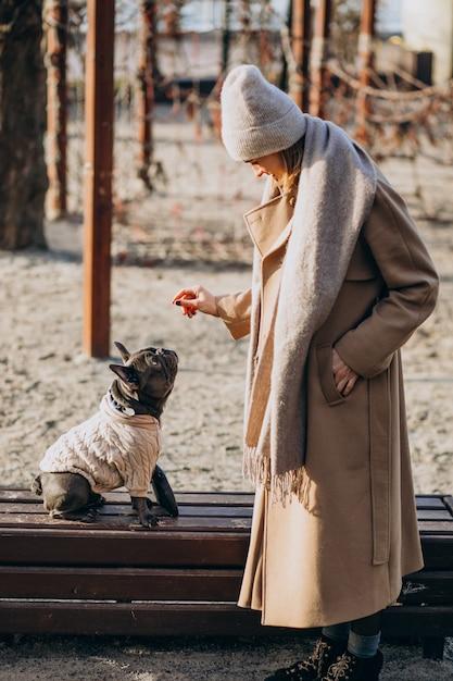Hermosa mujer con bulldog francés caminando en el parque Foto gratis
