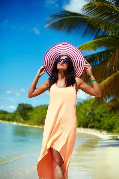 Hermosa mujer caliente en colorido sombrero para el sol y vestido caminando cerca de la playa del océano en un caluroso día de verano cerca de la palma Foto gratis