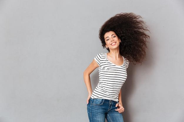 Hermosa mujer en camiseta a rayas divirtiéndose con agitando su hermoso cabello sonriendo siendo alegre y feliz sobre la pared gris Foto gratis