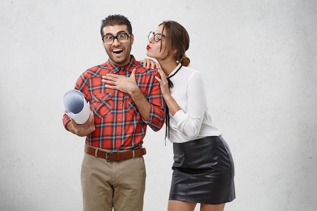 Hermosa mujer cariñosa va a besar a su novio. el hombre agradablemente sorprendido no espera tener tan buenas relaciones con su ex colega. Foto gratis