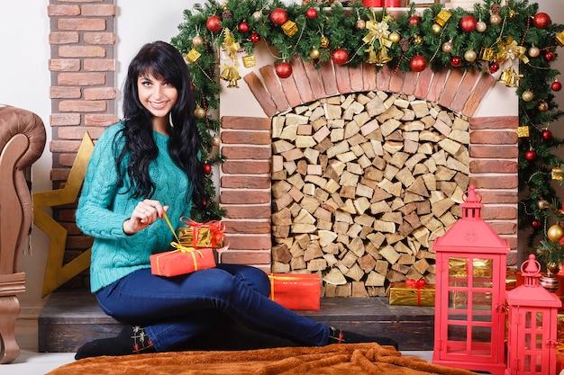 Hermosa mujer caucásica joven sentada cerca de una chimenea decorativa en un interior de navidad. Foto Premium