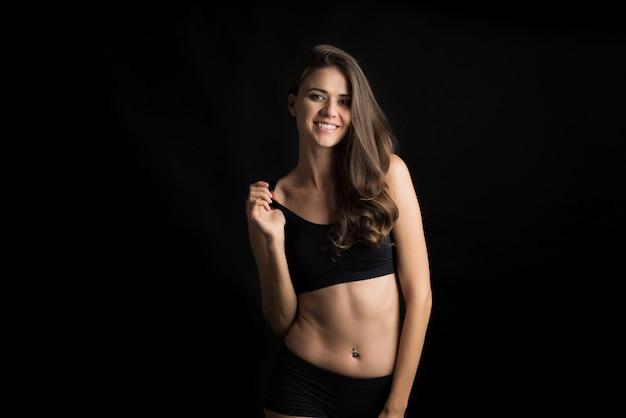 Hermosa mujer con cuerpo sano sobre fondo negro Foto gratis