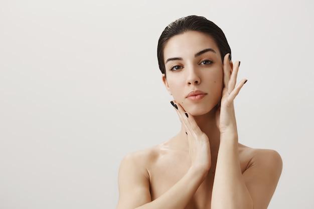 Hermosa mujer desnuda aplicar crema facial, tocando la cara suavemente Foto gratis