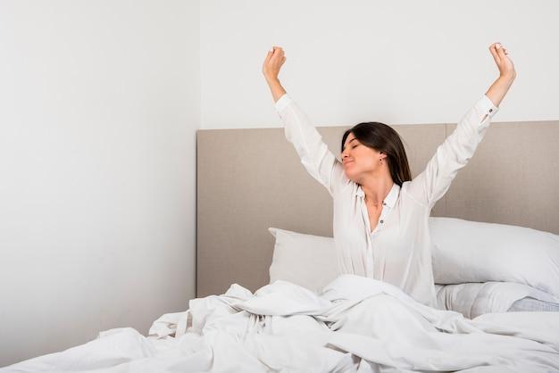 Hermosa mujer despertándose en su cama en el dormitorio. Foto gratis