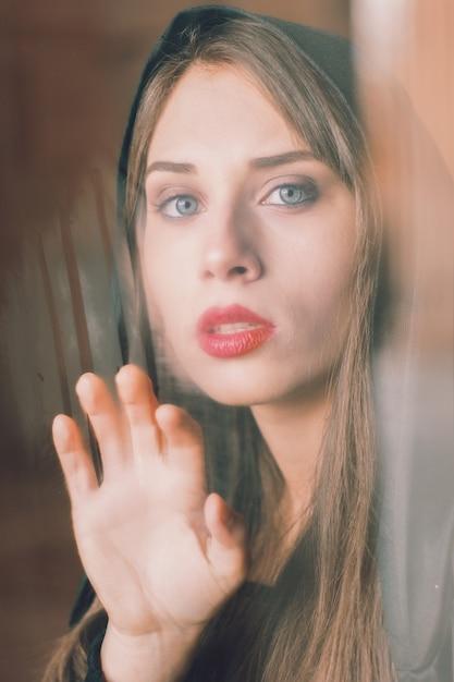 Una hermosa mujer detrás de la ventana | Foto Premium