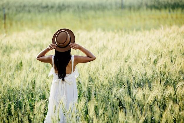 Hermosa mujer disfrutando en campos de cebada. Foto gratis