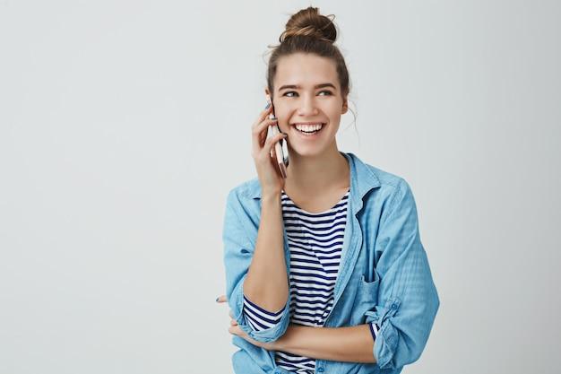 Hermosa mujer europea femenina riendo hablando por teléfono casualmente Foto gratis