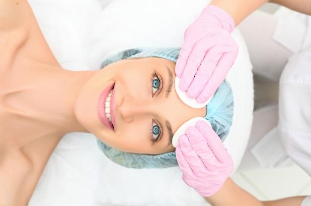 Hermosa mujer feliz recibiendo tratamiento de spa. cosmetóloga en salón de belleza limpieza de cara de mujer. belleza facial chica modelo de spa con piel limpia fresca perfecta. concepto de cuidado de la piel Foto Premium