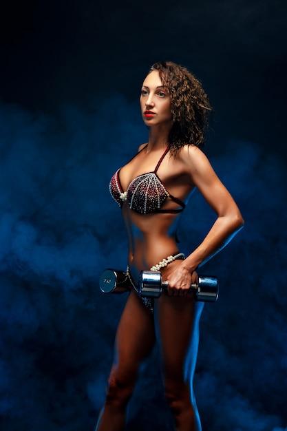 Hermosa mujer fitness levantamiento de pesas. Foto Premium