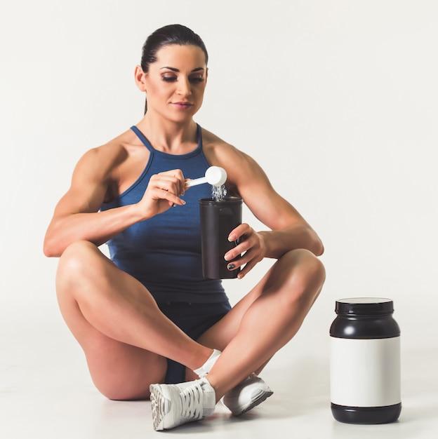 Hermosa mujer fuerte en ropa deportiva agregando nutrición deportiva. Foto Premium