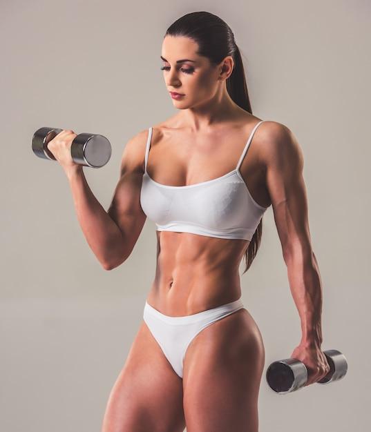 Hermosa mujer fuerte en ropa interior blanca con pesas. Foto Premium
