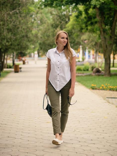 Hermosa mujer con gafas de sol en la mano izquierda camina por el sendero en el parque. Foto Premium