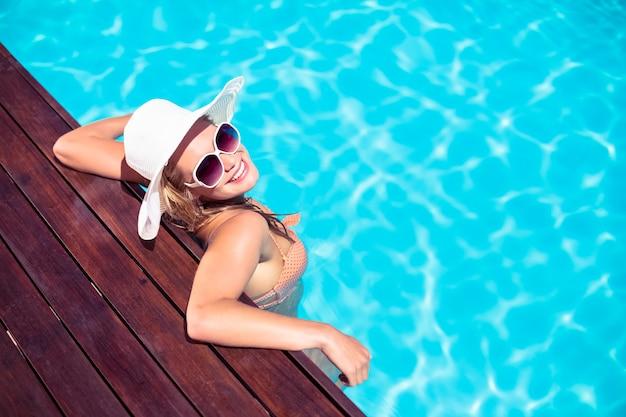 Hermosa mujer con gafas de sol y sombrero de paja, apoyado en la terraza de madera junto a la piscina Foto Premium