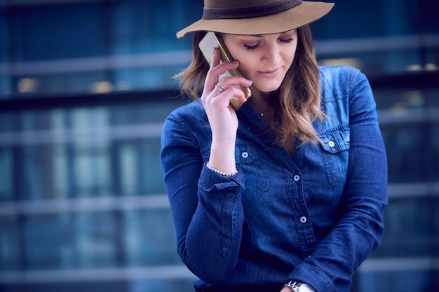 Hermosa mujer hablando con móvil en entorno urbano. Foto Premium