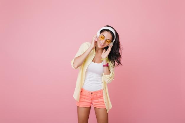 Hermosa mujer hispana en reloj de pulsera de moda escuchando música con los ojos cerrados. retrato interior de una increíble modelo femenina latina en pantalones cortos rosas disfrutando de la canción Foto gratis