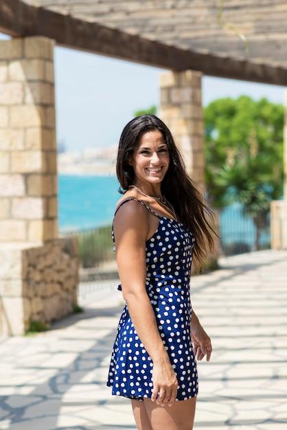Hermosa mujer hispana en vestido azul de pie al aire libre mientras mira a la cámara Foto Premium
