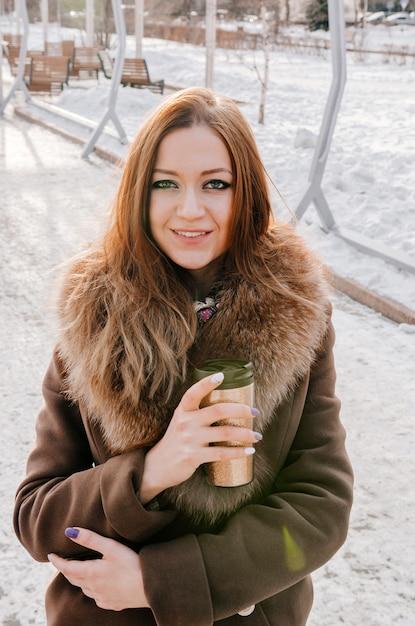 Hermosa mujer de jengibre bebiendo té caliente de termo taza Foto Premium