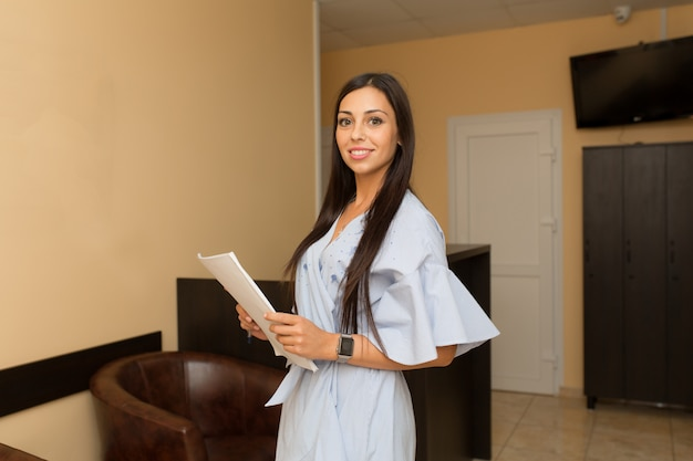 Hermosa mujer joven administrador en recepción mantenga carpeta con papeles. Foto Premium