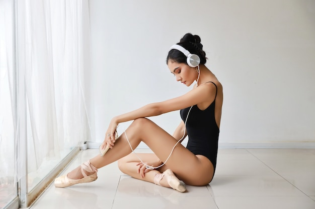 Hermosa mujer joven asiática sana y deportiva en ropa deportiva negra con auriculares, escuchando música desde el teléfono móvil mientras entrena ballet Foto Premium