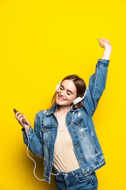 Hermosa mujer joven en auriculares escuchando música y bailando en la pared amarilla Foto gratis