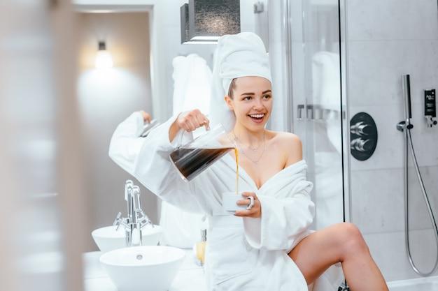 Hermosa mujer joven en bata de baño y una toalla sobre su cabeza sentada en una bañera Foto gratis