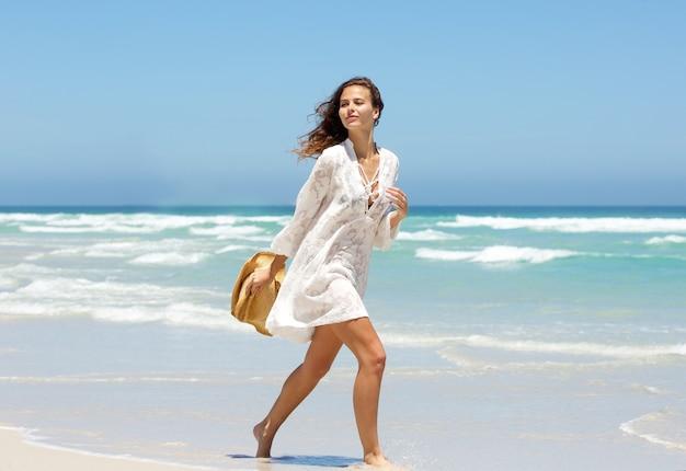 f76d1b4c01 Hermosa mujer joven caminando en la playa en el vestido de verano ...