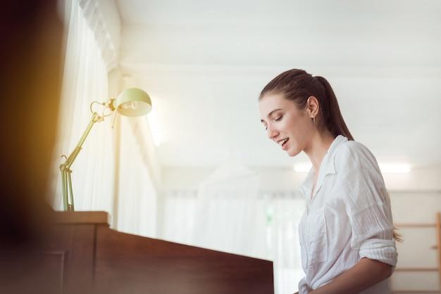 Hermosa mujer joven caucásica tocando piano eléctrico, feliz y sonriente, tiempo relajante Foto Premium