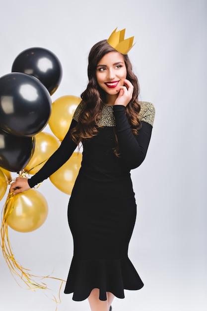 Hermosa mujer joven elegante en vestido de moda celebrando la fiesta de año nuevo, sosteniendo globos dorados y negros. tiene cabello largo castaño, corona amarilla. divirtiéndose, noche mágica, cumpleaños. Foto gratis