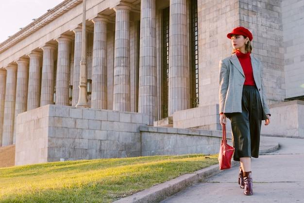 Hermosa mujer joven con gorra roja y bolso mirando a otro lado Foto gratis