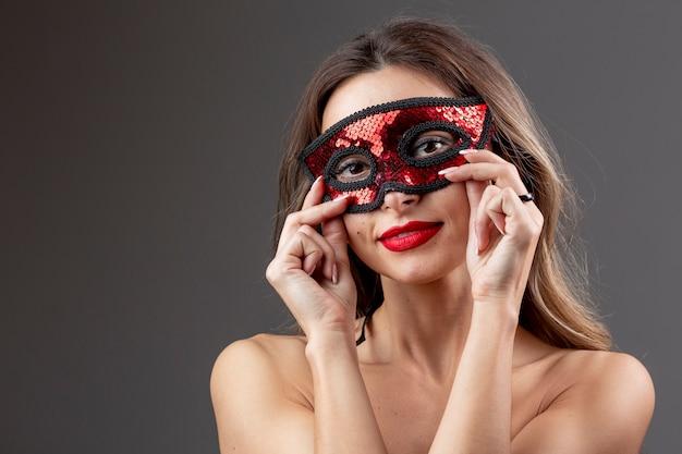 Hermosa mujer joven con máscara de carnaval Foto gratis