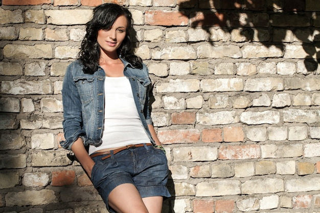 Hermosa mujer joven en la pared de ladrillo Foto gratis