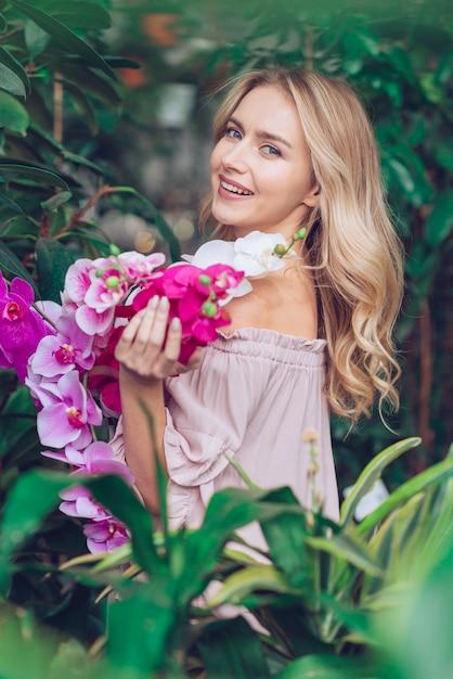 Hermosa mujer joven de pie cerca de las plantas con ramas de orquídea Foto gratis