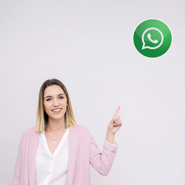 Hermosa mujer joven de pie contra el fondo blanco apuntando al icono de whatsup Foto gratis
