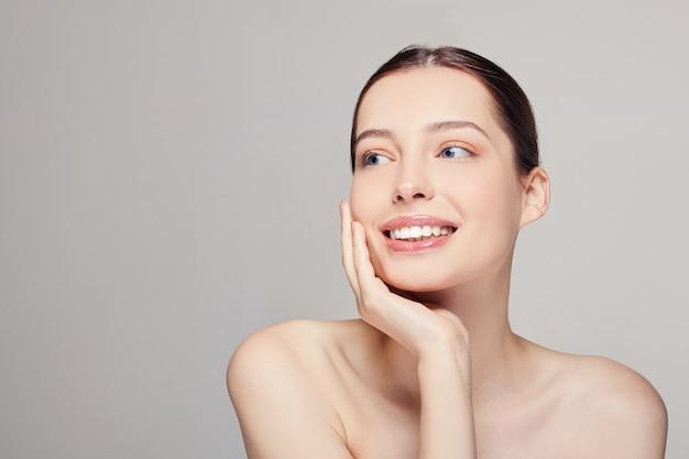 Hermosa mujer joven con piel limpia y fresca, ojos azules y oscuros oyen sonreír Foto Premium