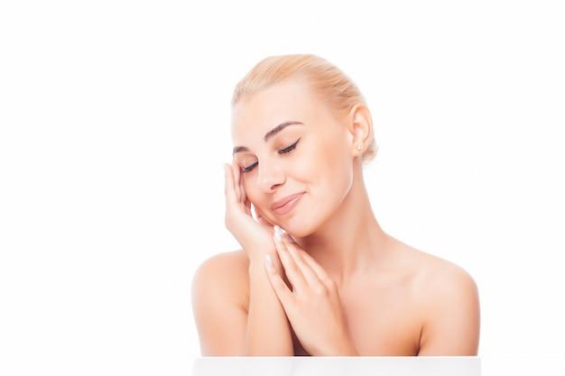 Hermosa mujer joven con piel limpia y fresca toque su propio rostro. tratamiento facial . cosmetología, belleza y spa. Foto gratis