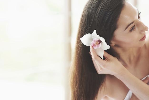 Hermosa mujer joven posando con orquídeas. tratamiento para el cuidado de la piel. Foto gratis