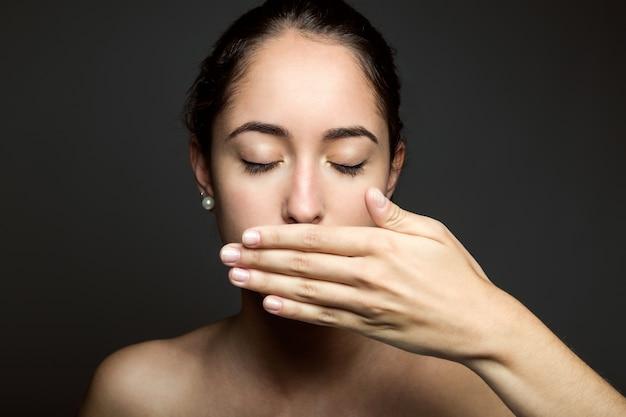 Hermosa mujer joven que cubre su boca con la mano. aislado. Foto gratis
