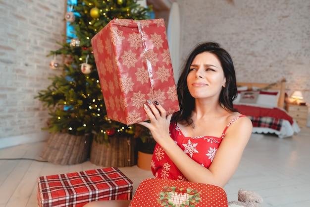 Hermosa mujer joven con regalos en el árbol de navidad Foto gratis