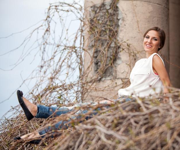 Hermosa mujer joven sentada en una vid Foto gratis