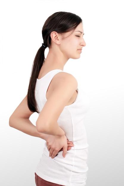 Hermosa mujer joven siente fuerte dolor de columna, tiene problemas de salud Foto Premium