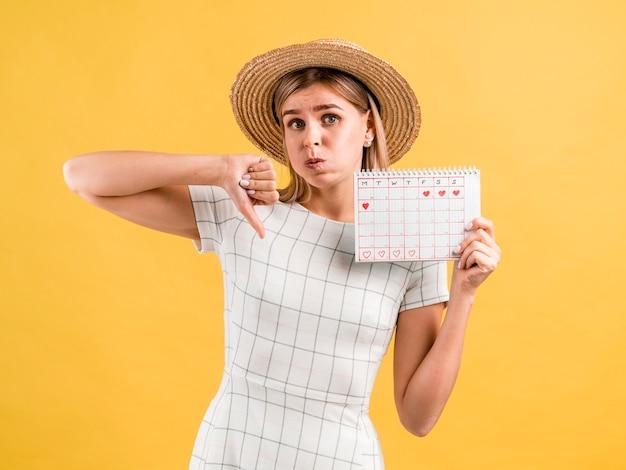 Hermosa mujer joven con sombrero pulgares abajo Foto gratis