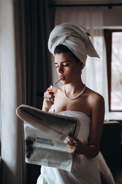 Hermosa mujer joven en una toalla fuma un cigarrillo y lee el periódico Foto gratis