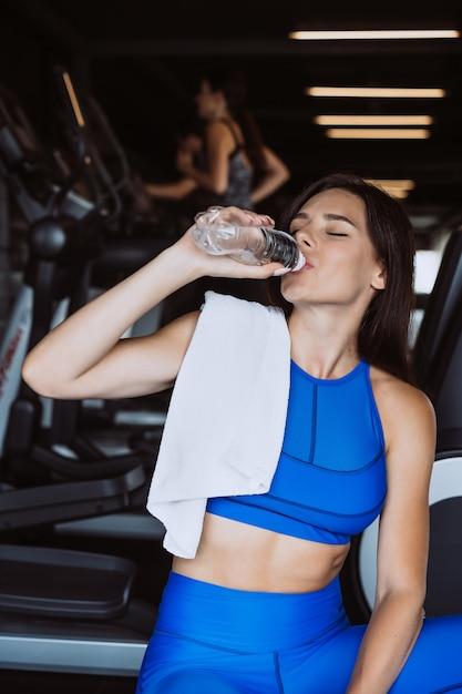 Hermosa mujer joven con una toalla sobre su hombro bebiendo agua de una botella en el gimnasio Foto gratis