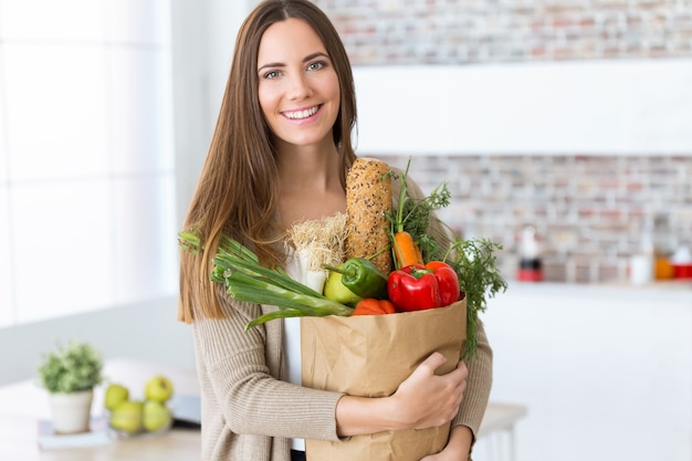 Hermosa mujer joven con verduras en bolsa de compras en casa. Foto gratis