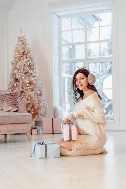 Hermosa mujer joven en vestido blanco posando con cajas de regalo Foto gratis