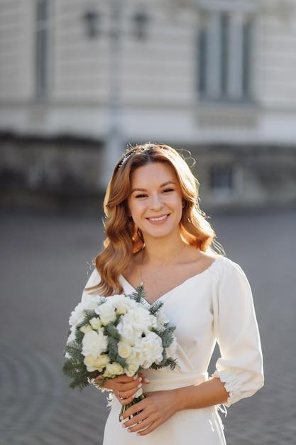 Hermosa mujer joven en vestido de novia posando en la calle en la ciudad Foto gratis