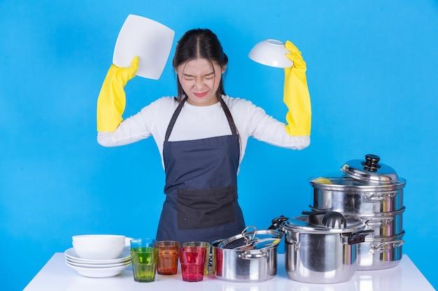 Una hermosa mujer lavando platos frente a él en un azul. Foto gratis