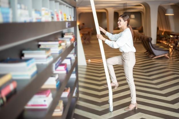 Hermosa mujer está leyendo libros en la biblioteca Foto Premium